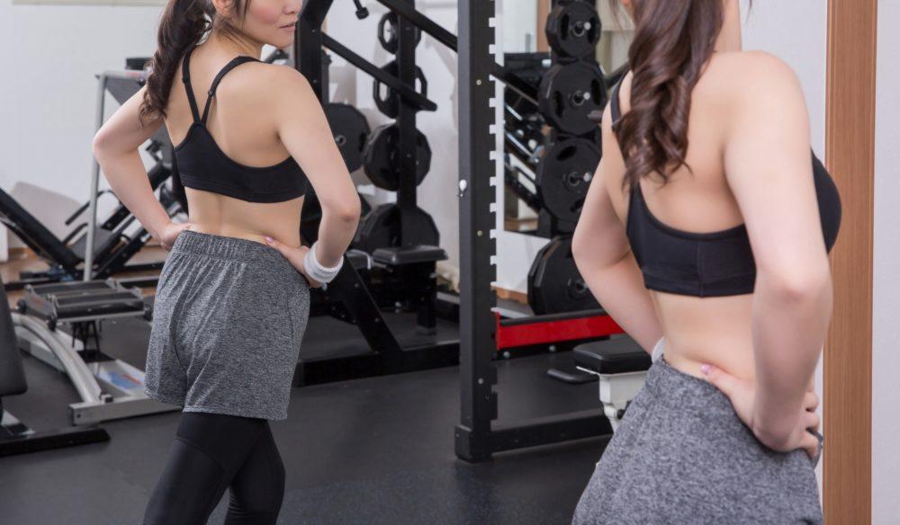 大きな鏡に自分の姿を映し、体型を気にする女性