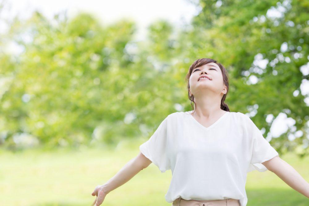 腕を広げ深呼吸する女性
