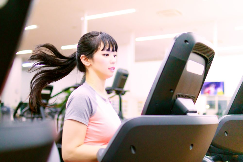 ランニングマシンでトレーニングを行う女性